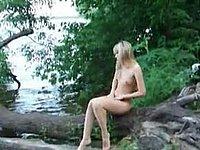 Junge Blondine nackt am See