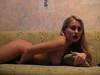 Junge geile Blondine nackt in Stiefeln auf der Couch