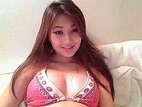 Hübsche junge Asiatin posiert nackt vor der Webcam
